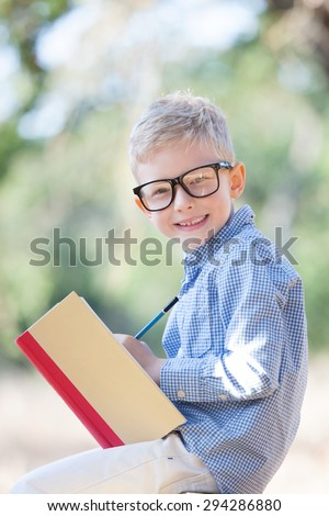 cheerful boy in glasses holding book and pencil studying and ready for school - stock photo