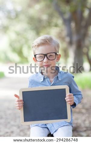 cheerful boy in glasses holding empty blackboard, ready for school - stock photo