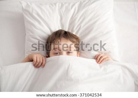 Cheerful boy in white bed under white blanket. Sleeping boy. Sleeping child - stock photo