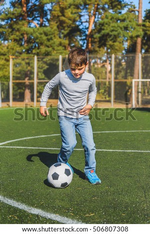 Cheerful boy is playing football on field with aspiration