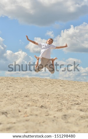 Cheerful boy jumping on sand against blue sky - stock photo
