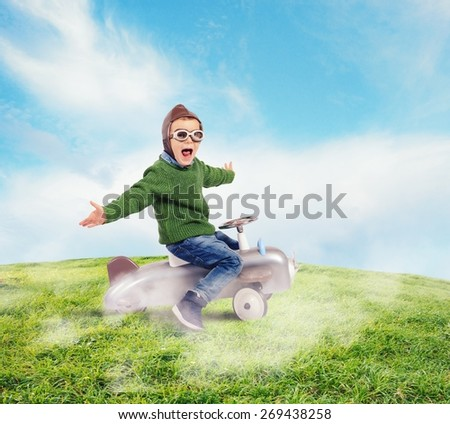 Cheerful boy kid playing at the aviator - stock photo