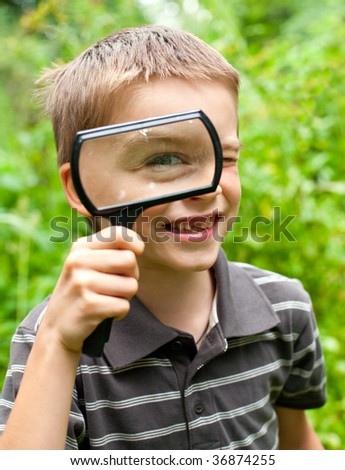 Cheerful boy looking through hand magnifier, shallow DOF - stock photo