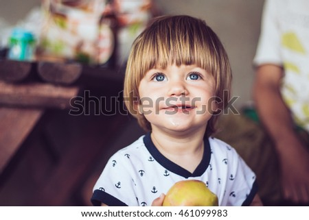 Cheerful boy offering an apple, and looking up with wide opened smile.