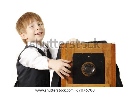 cheerful boy retro photographer with vintage camera in studio isolated on white background - stock photo