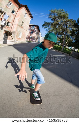 Cheerful boy riding a skateboard on the street. Fish-eye lens. - stock photo