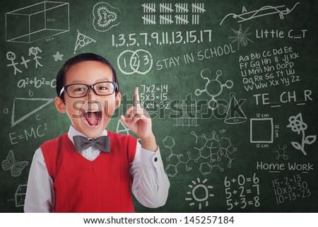 Cheerful boy student has idea in classroom - stock photo