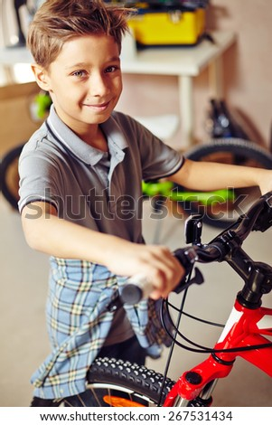 Cheerful boy with bicycle looking at camera - stock photo
