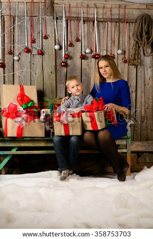 cheerful boy with her mother with Christmas gift in hands