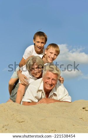 Cheerful boys with their grandparents on the sand in the summer - stock photo