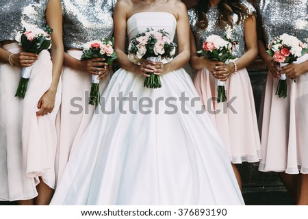 Cheerful bride & bridesmaids with bouquets posing outdoors closeup - stock photo