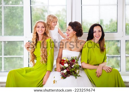 Cheerful bride holding bouquet with female friends and little flower girl - stock photo