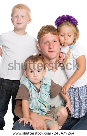 Cheerful brothers and sister sitting and embracing on the carpet - stock photo
