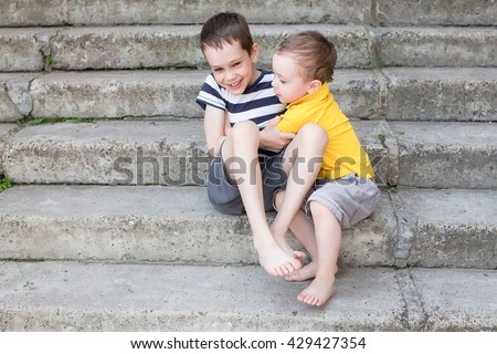 cheerful brothers playfully fighting and tickle each other. Two laughing boys hugging and tickling each other on the stairs - stock photo