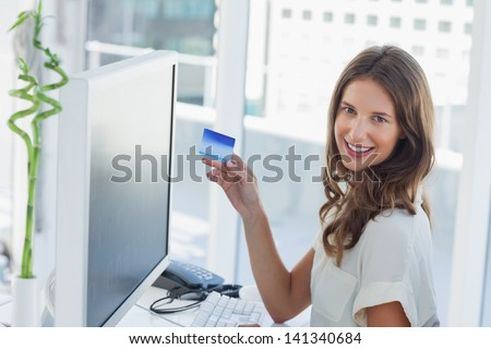 Cheerful brunette designer purchasing online with her credit card - stock photo
