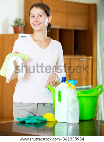 Cheerful brunette girl dusting furniture at home and smiling  - stock photo