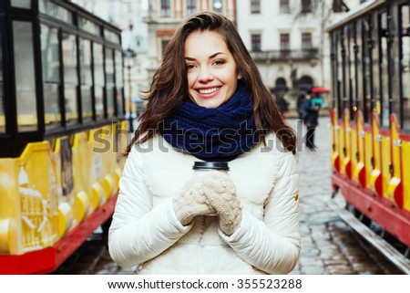 Cheerful brunette girl, with long curly hair, wearing in white coat, blue scarf and gloves, posing between two red and yellow trams with cup of coffee, on the street of old European city, waist up - stock photo