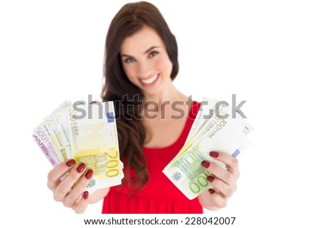 Cheerful brunette showing her cash money on white background