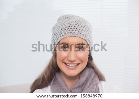 Cheerful brunette with winter hat on posing in bright living room - stock photo