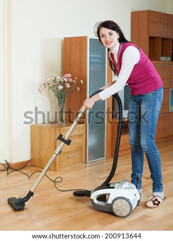 cheerful brunette woman cleaning with vacuum cleaner on parquet floor at home