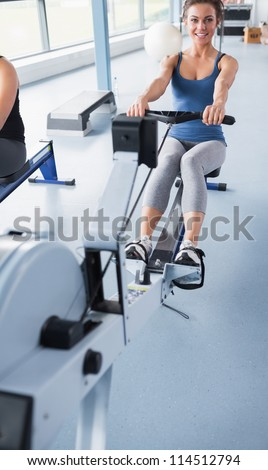 Cheerful brunette woman training on row machine - stock photo