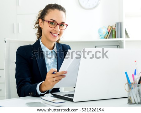 Cheerful business lady sitting at office desk with laptop