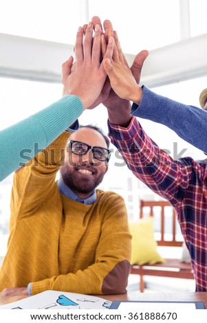 Cheerful Business man doing high five with team in creative office - stock photo