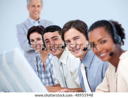 Cheerful business partners working with their manager in a call center - stock photo