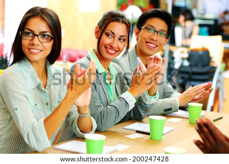 Cheerful business people applauding in a meeting. Business concept.
