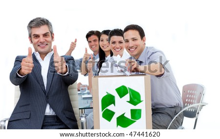 Cheerful business people showing the concept of recycling against a white background
