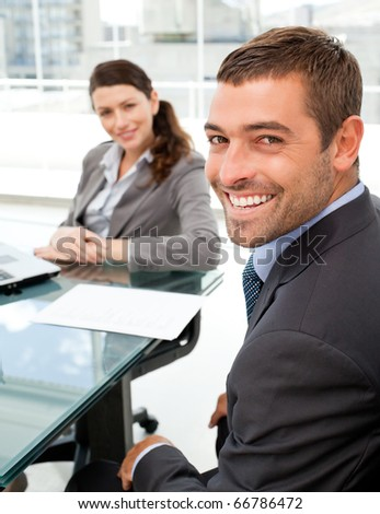 Cheerful business people sitting at a table with a laptop during a meeting
