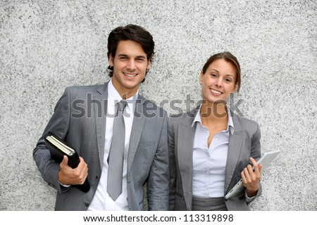 Cheerful business people standing on grey background - stock photo