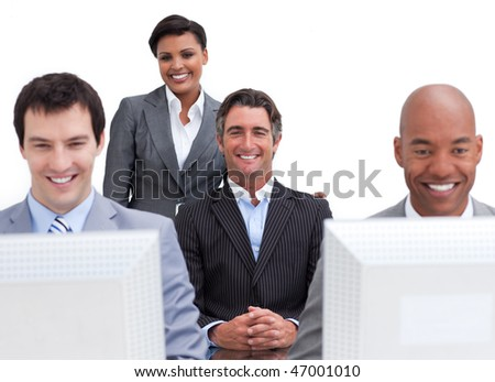 Cheerful business people working at computers in the office - stock photo