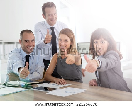 Cheerful business team showing thumbs up - stock photo