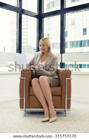 Cheerful business woman sitting in a chair. Working on laptop in modern office - stock photo