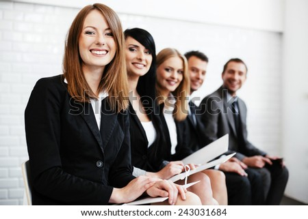 Cheerful business woman sitting wiht other professionals waiting for interview - stock photo