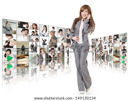 Cheerful business woman talk on phone and stand in front of tv wall, concept about business, teamwork, talk,connect, social media etc.