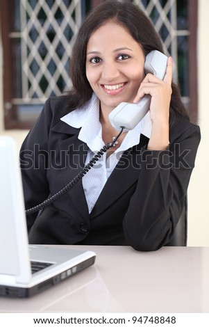 Cheerful business woman talking on phone - stock photo