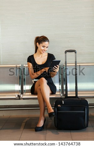 cheerful business woman using tablet computer at airport - stock photo