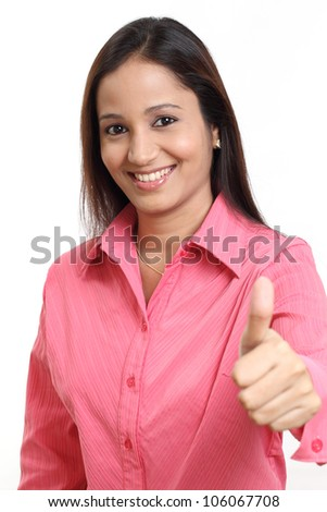 Cheerful business woman with thumbs up gesture - stock photo