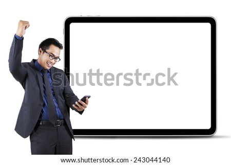 Cheerful businessman celebrate his success while reading good news on cellphone in front of empty board - stock photo