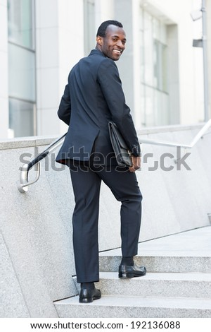 Cheerful businessman. Cheerful young African man in formal wear moving up by staircase and looking over shoulder  - stock photo