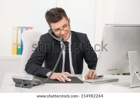 Cheerful businessman. Cheerful young man in formalwear sitting at his working place and talking on the phone - stock photo