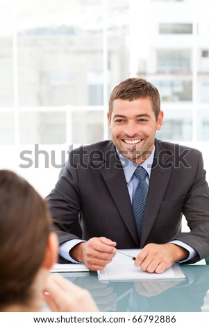 Cheerful businessman during a meeting with a collegue sitting around a table