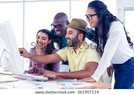 Cheerful businessman explaining colleagues over computer at creative office - stock photo