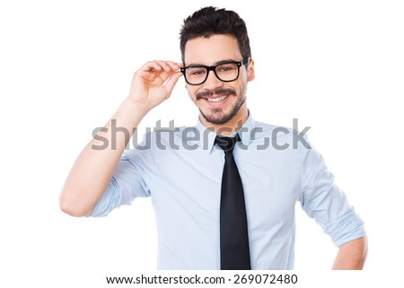 Cheerful businessman. Handsome young man in shirt and tie adjusting his eyeglasses and smiling while standing against white background - stock photo