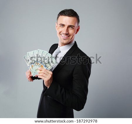 Cheerful businessman holding group of dollar bills on a gray background - stock photo