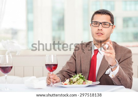 Cheerful businessman is sitting at the table in cafe. He is calling for waitress with seriousness. He is drinking red wine with pleasure. Copy space in left side - stock photo