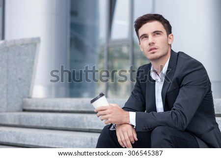 Cheerful businessman is sitting on steps outdoors. He is drinking coffee and relaxing. The man is looking up dreamingly. Copy space in left side