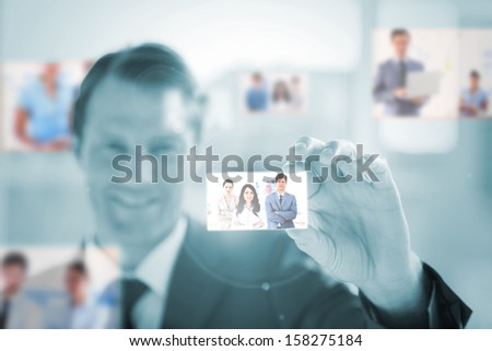 Cheerful businessman picking a picture on blue background - stock photo